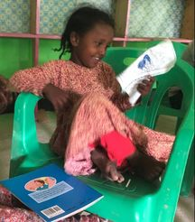 Little girl sitting in a chair reading a book